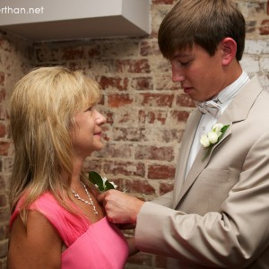 Groom pinning corsage on his Mother